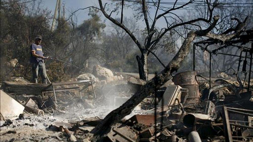 Una residente de la localidad de Ein Hod ayuda en las labores de extinción del incendio declarado en el bosque de Carmel, cerca de Haifa, norte de Israel. EFE
