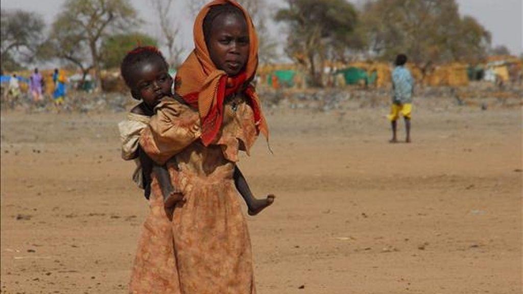 Dos niñas cruzan una tierra reseca en un campo de refugiados, el cual está ocupado por 120.000 personas que han salido de villas aledañas, luego de los enfrentamientos entre el SLA (Ejército de Liberación de Sudán), fuerzas del gobierno y la milicia Janjaweed, en Gereida (Sudán). EFE/Archivo