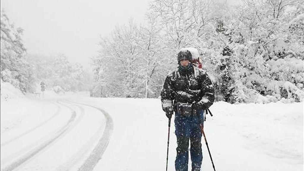 Un peregrino camina por la N-135, en el alto de Erro, en Navarra, durante una intensa nevada que cubrió hoy la carretera. EFE