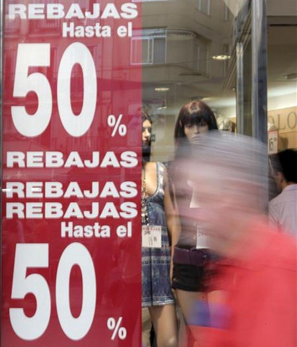 Un hombre pasa delante de un escaparate con un cartel de rebajas, que comenzarán en las tiendas de toda España el 1 de julio, después de que lo hicieran la pasada semana las de Madrid y Castilla La Mancha. EFE/Archivo