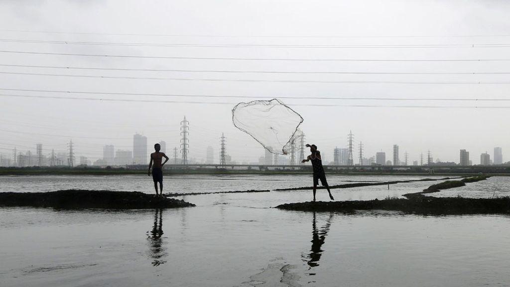 Un hombre pasa la red de pesca a otro en India