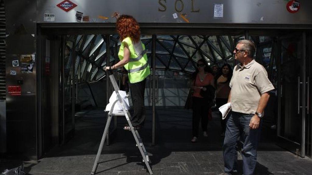 Una voluntaria despega carteles de la salida del metro