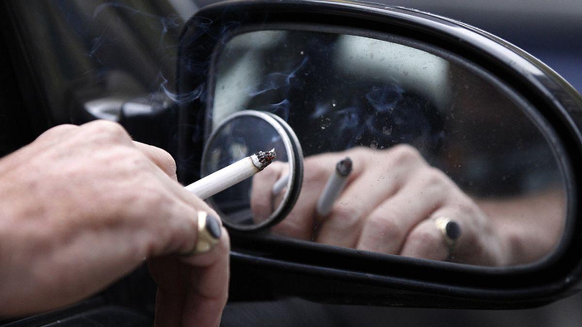 Un hombre conduce mientras fuma