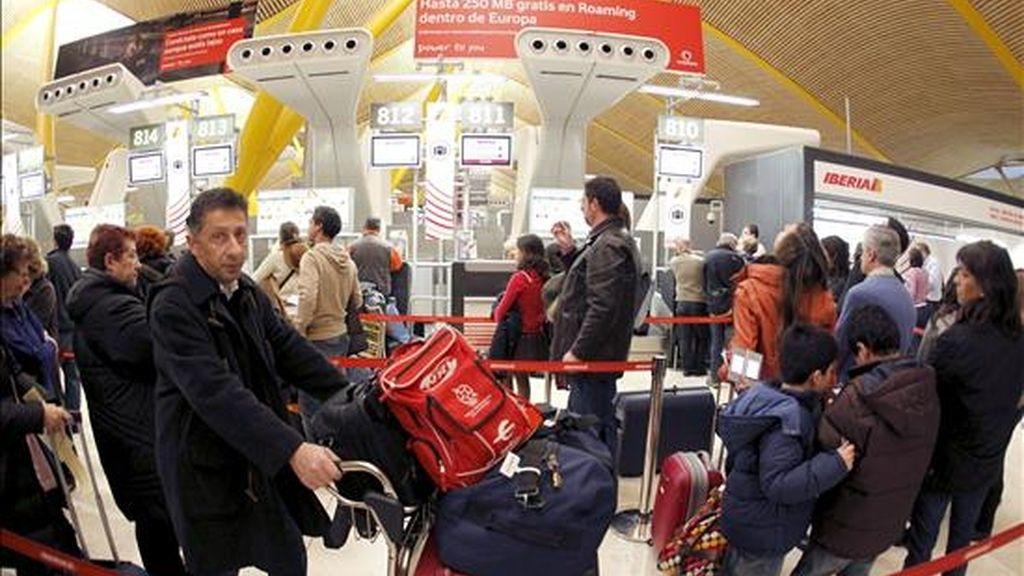 Cientos de personas esperan la salida de los primeros vuelos de la mañana en el aeropuerto de Madrid-Barajas, que aún sufren retrasos y pocas cancelaciones, aunque casi la totalidad de las aerolíneas factura regularmente. EFE