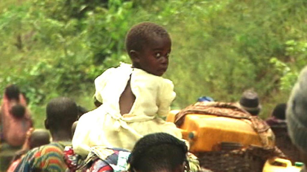 Una niña cansa es transportada a hombros por su padre
