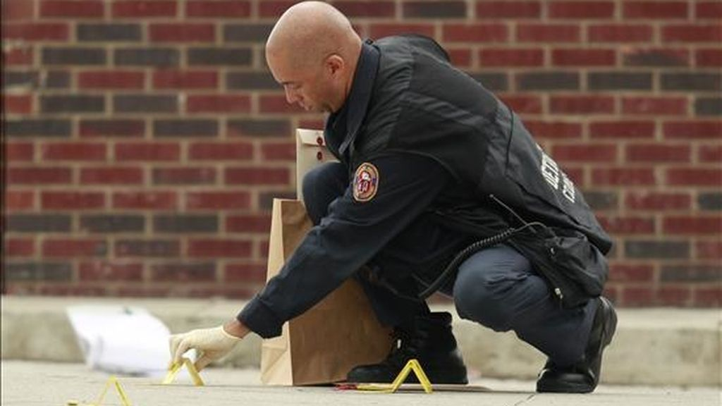 Imagen de este martes de un oficial de la policía de Detroit mientras recoge evidencias en el área donde siete personas recibieron disparos. EFE