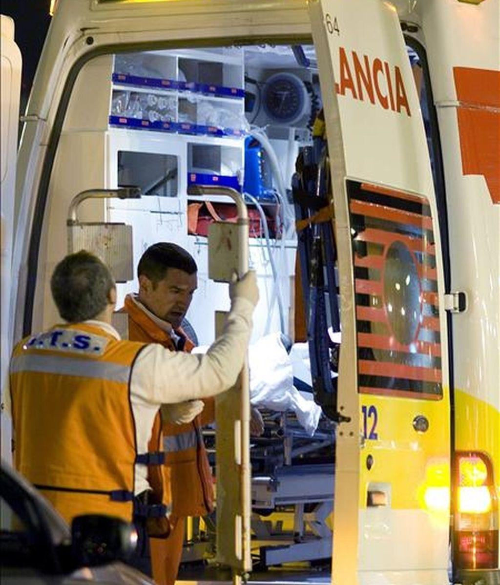 Dos sanitarios atienden a una persona en una  ambulancia. EFE/Archivo