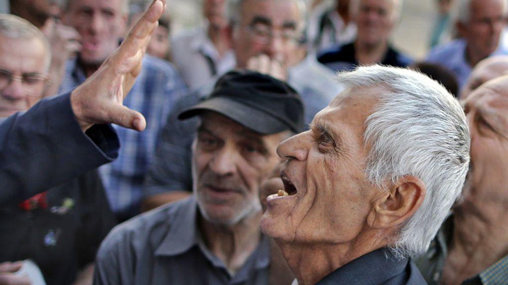 Un jubilado griego exige su pensión a las puertas de un banco