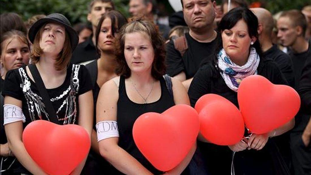 Unas jóvenes sosteniendo globos en forma de corazón durante una manifestación en memoria de las veintiuna víctimas de la Loveparade en Duisburgo (Alemania) este sábado. EFE