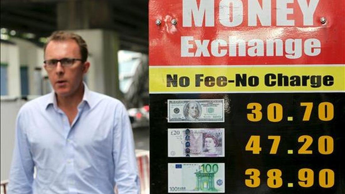 Un hombre camina junto a un tablero con los valores de distintas divisas en el distrito financiero de Bangkok. EFE/Archivo