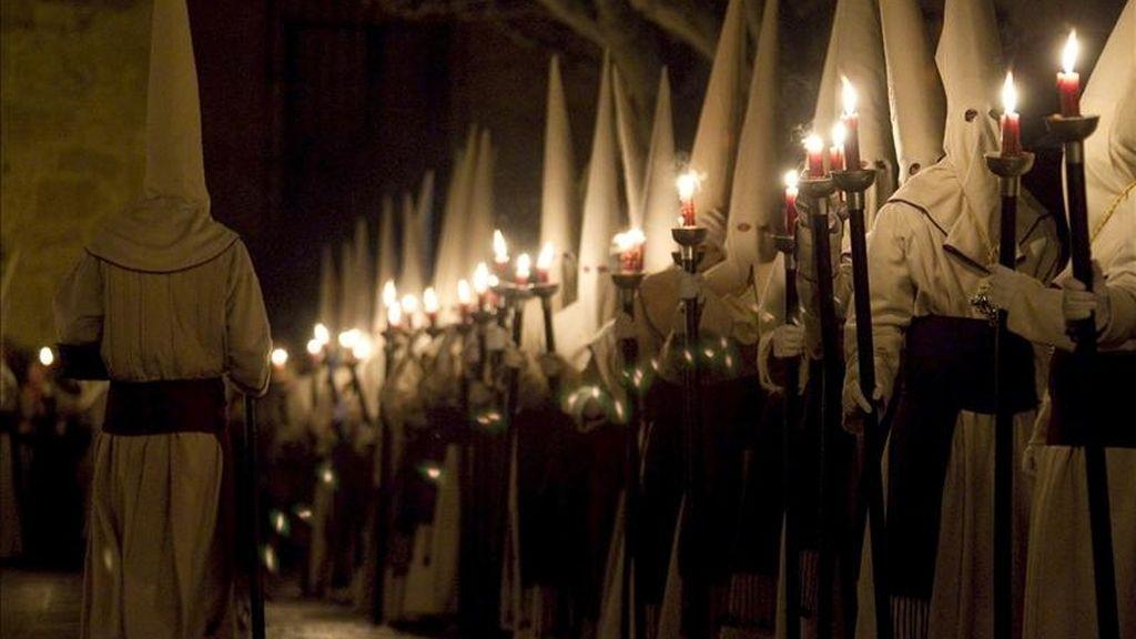 """Cofrades congregados en la plaza de Viriato de Zamora, durante la pasada noche, entonan el """"Canto del Miserere"""" en la procesión de la Penitente Hermandad de Jesús Yacente. EFE"""