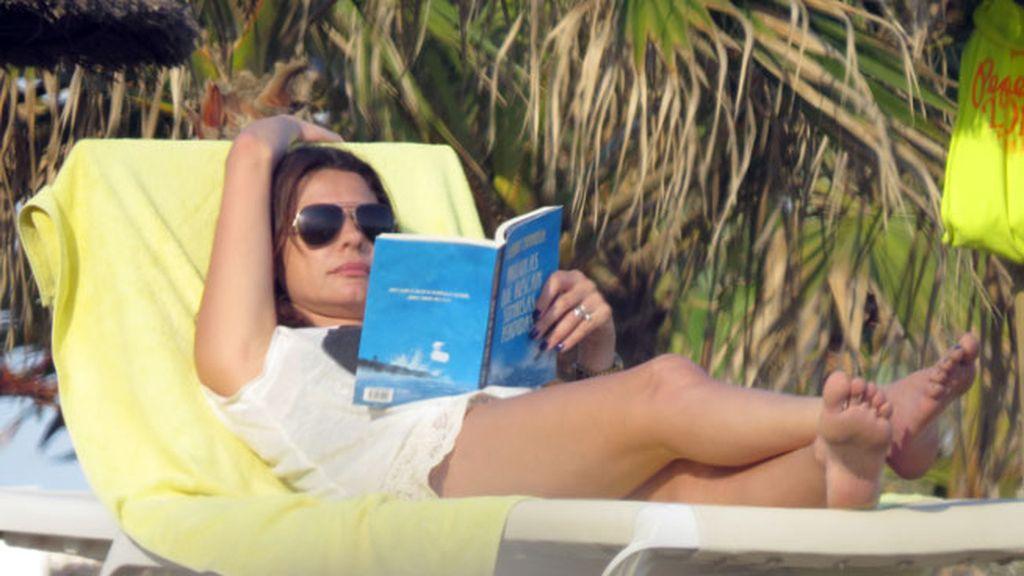 María José Suárez se distrae leyendo en la tumbona