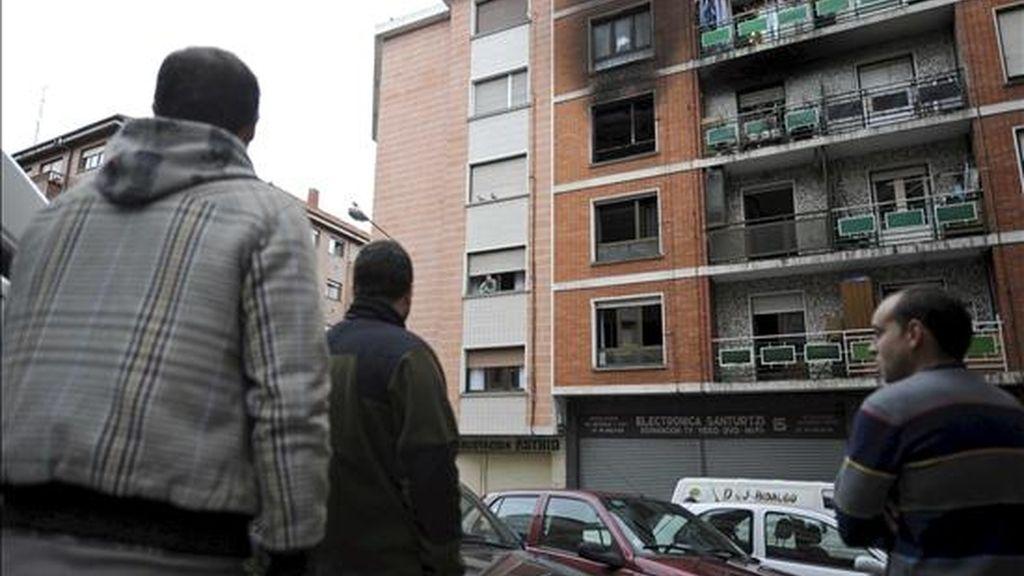 Varias perosnas observan desde la calle los daños causados en una vivienda de la calle Doctor Fleming de la localidad vizcaína de Santurtzi, donde una persona ha muerto esta mañana a causa de un incendio. EFE