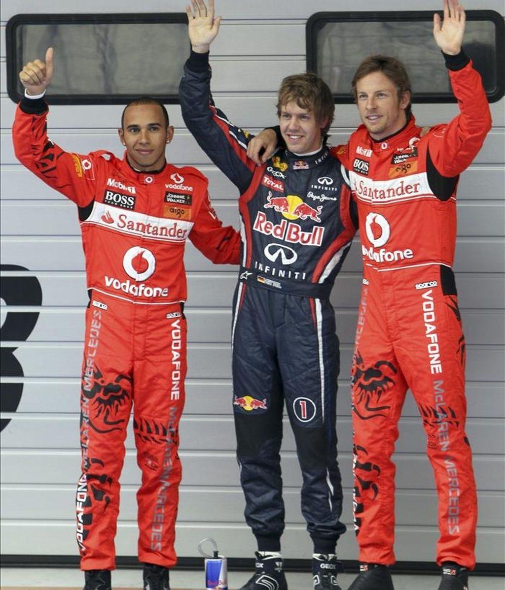 El piloto alemán de Fórmula Uno Sebastian Vettel (c), de la escudería Red Bull Racing, saluda a sus aficionados después de lograr la pole en la sesión clasificatoria del Gran Premio de China de Fórmula Uno, por delante de los británicos Jenson Button (d) y Lewis Hamilton (d), ambos de la escudería McLaren Mercedes, en Shanghái (China), hoy. EFE
