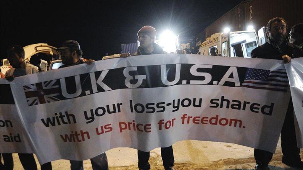 Foto disponible desde hoy que muestra a un grupo de hombres portando una pancarta durante la llegada a Bengasi de un barco griego con inmigrantes evacuados de la sitiada ciudad libia de Misrata. EFE