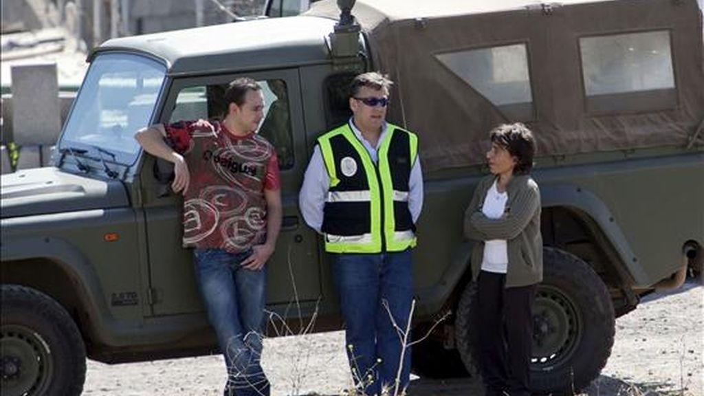 La madre de la joven desaparecida Sara Morales, Nieves Hernández, dialoga con dos agentes del Cuerpo Nacional de Policía, mientras a unos metros se remueve la tierra de un solar próximo al Centro Comercial, en el que fue vista por última vez, en busca de posibles restos de la chica. EFE/Archivo