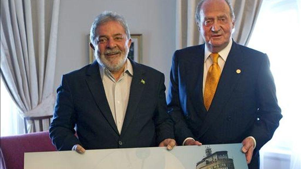 El presidente brasileño, Luiz Inácio Lula da Silva (i) junto al Rey Juan Carlos posan a un foto de Sao Paulo, realizada por el fotógrafo y pintor madrileño José Manuel Ballester, al inicio de la reunión que ambos han mantenido durante la XX Cumbre Iberoamericana de Jefes de Estados y de Gobierno, que se celebra en Mar del Plata, Argentina. EFE