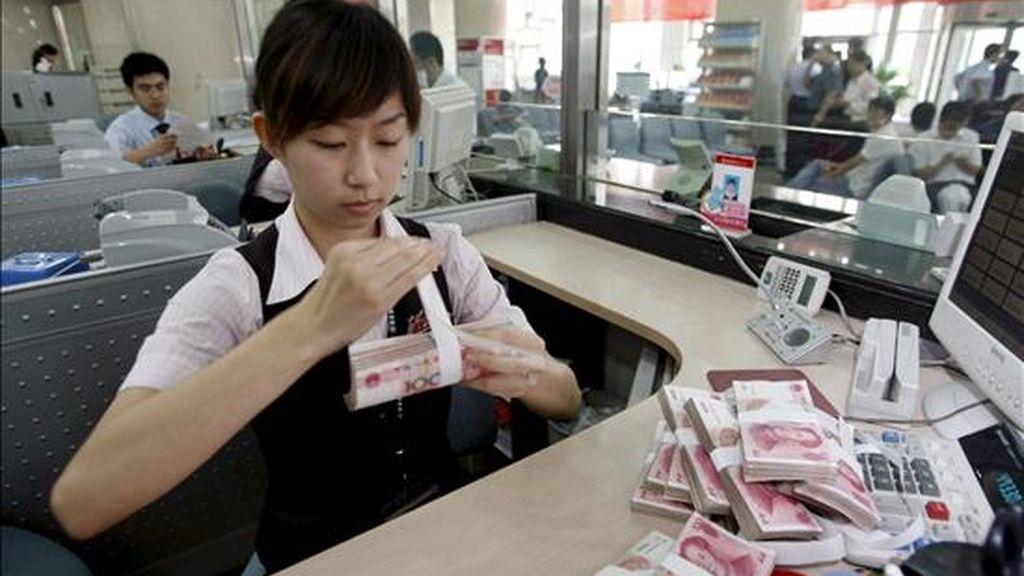 Una empleada del Banco Comercial de China cuenta billetes de 100 yuan en una sucursal de Pekín. EFE/Archivo