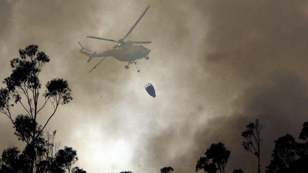 Un helicóptero descarga agua sobre uno de los frentes del incendio forestal en Boiro (A Coruña)