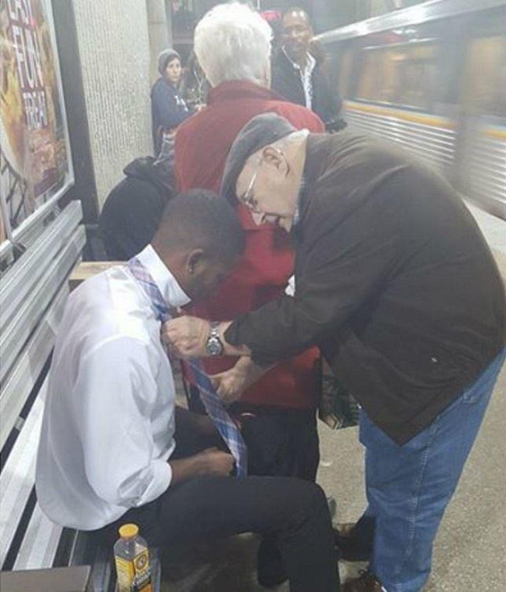 Un hombre le enseña a un joven cómo atarse una corbata en el metro