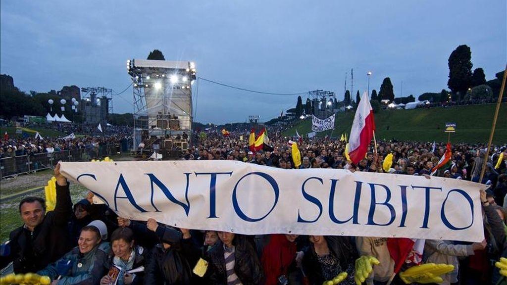 """Peregrinos con un cartel en el que se lee """"pronto santo"""" hoy en el Circo Massimo, de Roma, durante la noche de vigilia de la beatificación del papa Juan Pablo II. EFE"""