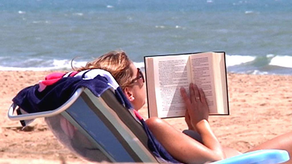 Una mujer que lee tranquilamente mientras toma el sol en la Playa