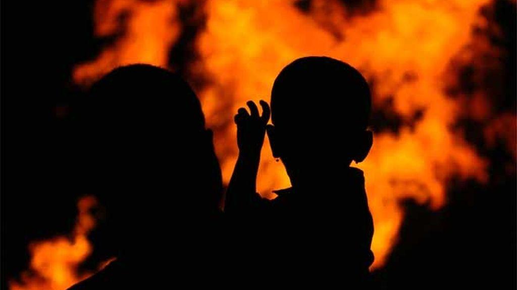 """Un hombre sostiene a su hijo mientras ven una hoguera ritual que marca el comienzo de """"Holi"""" el festival hindú de color en Bombay"""