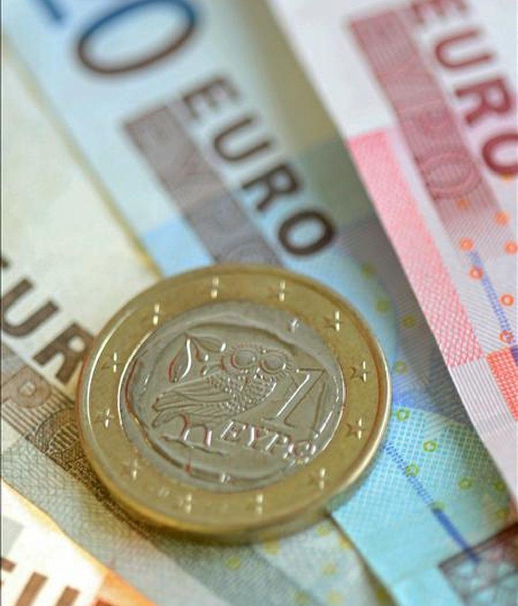 Una moneda griega de un euro sobre varios billetes, fotografiada en Fráncfort del Meno, Alemania. EFE/Archivo