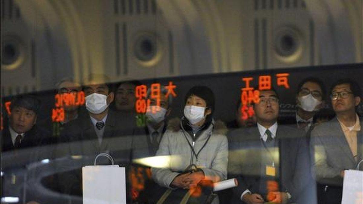 Visitantes observan los indicadores electrónicos con las cifras de la Bolsa de Valores de Tokio durante una jornada mercantil. EFE/Archivo