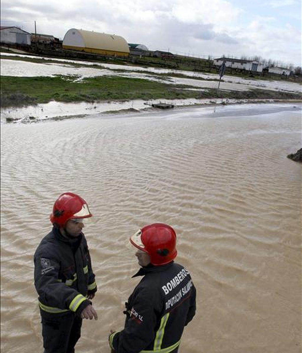 Dos miembros del cuerpo de Bomberos trabajan en la localidad salmantina de Forfoleda, donde las abundantes lluvías caídas han originado el desbordamiento de un arroyo que ha inundado varias calles del municipio. EFE