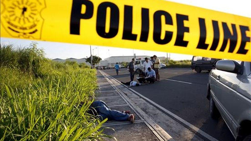 Investigadores filipinos examinan el 10 de junio, el cuerpo de un presunto secuestrador asesinado en un tiroteo con la policía en Paranaque, sur de Manila (Filipinas). EFE