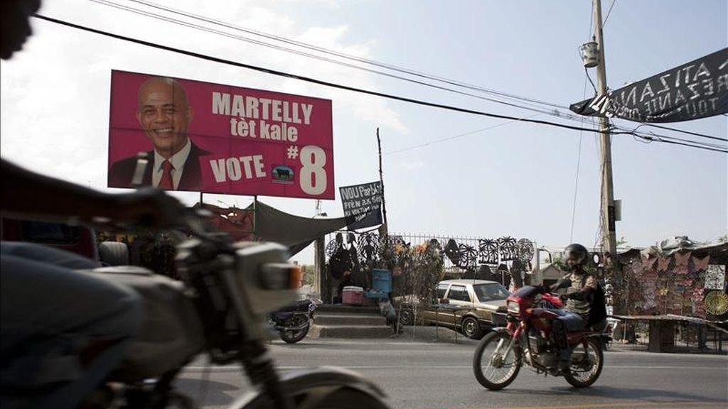 Motociclistas transitan en frente de un cartel electoral del candidato presidencial del partido Repons Peyizan, Michel Martelly, en la Avenida Panamericana de Puerto Príncipe (Haití). La OEA entregó ayer al Gobierno de Haití el informe definitivo de la misión de expertos que verificó el resultado de las elecciones del pasado 28 de noviembre de 2010. EFE