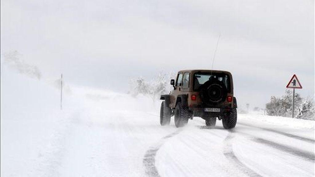 Un coche a su paso por O Cebreiro (Galicia), intenta circular por la carretera LU-633, en dirección a Sarria, a pesar de la nieve que cubre toda la vía. EFE