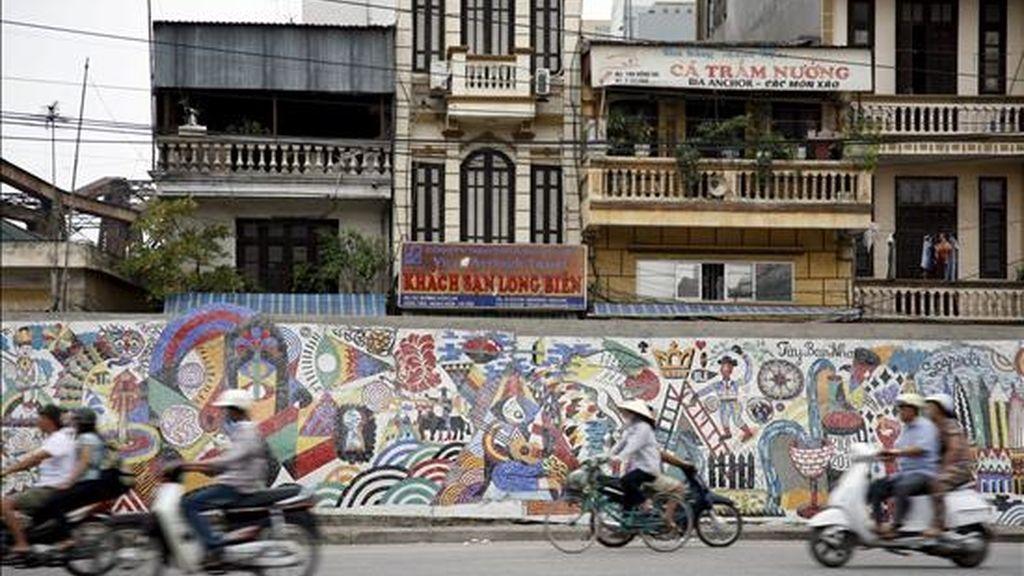 Fotografía facilitada por el artista callejero 3TTman (Trois Tête man) que ha transformado un desangelado muro gris a orillas del río Rojo a su paso por Hanoi en una obra de arte moderna y en un nuevo icono de la capital vietnamita, por iniciativa de España. EFE