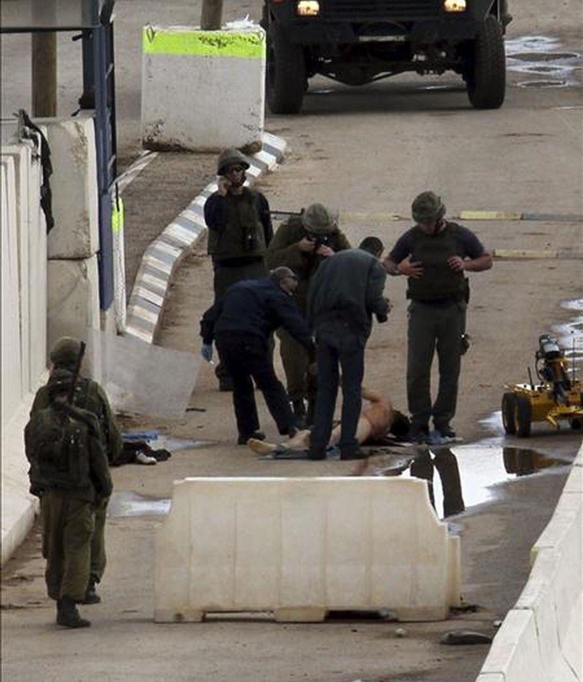Soldados israelíes rodean el cadáver del joven palestino Khaldon Samodi, supuestamente muerto tras ser disparado por los soldados en el puesto de control fronterizo de Hamra, al este de Naplusa (Cisjordania), hoy, 8 de enero de 2011. EFE