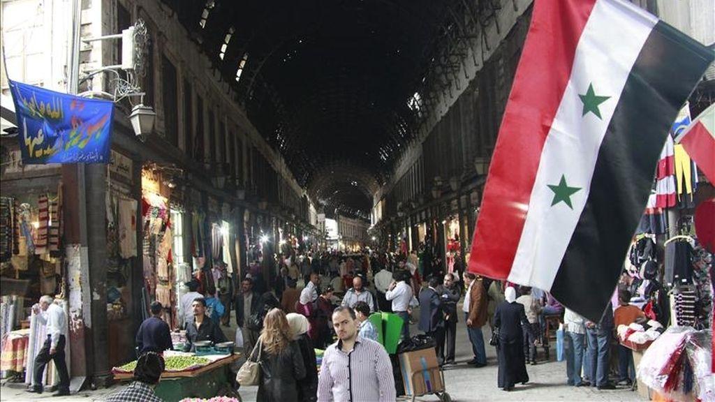 Una bandera nacional siria cuelga de una de las paredes de un zoco de Damasco hoy, durante una visita guiada de las autoridades sirias a periodistas locales para desmentir las denuncias de que el país está convulsionado por las protestas para expulsar al Gobierno. EFE