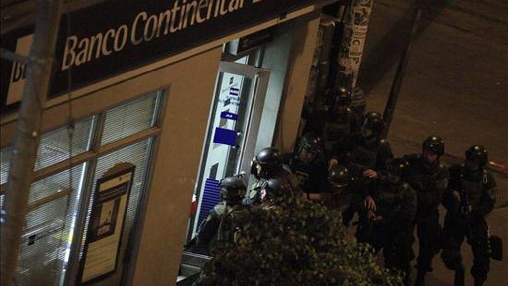 Policías entran a una sucursal del banco BBVA para dar fin a una toma de rehenes realizada en la zona comercial de Gamarra en Lima (Perú). EFE
