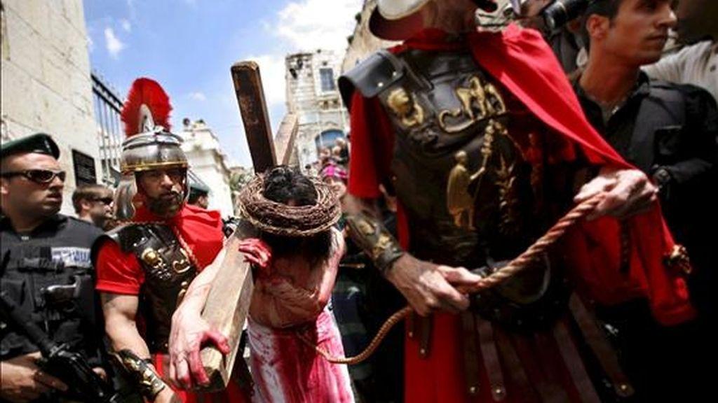 Un hombre que representa a Jesucristo cargando la cruz durante una procesión de Viernes Santo hoy en la Vía Dolorosa de Jerusalén. EFE
