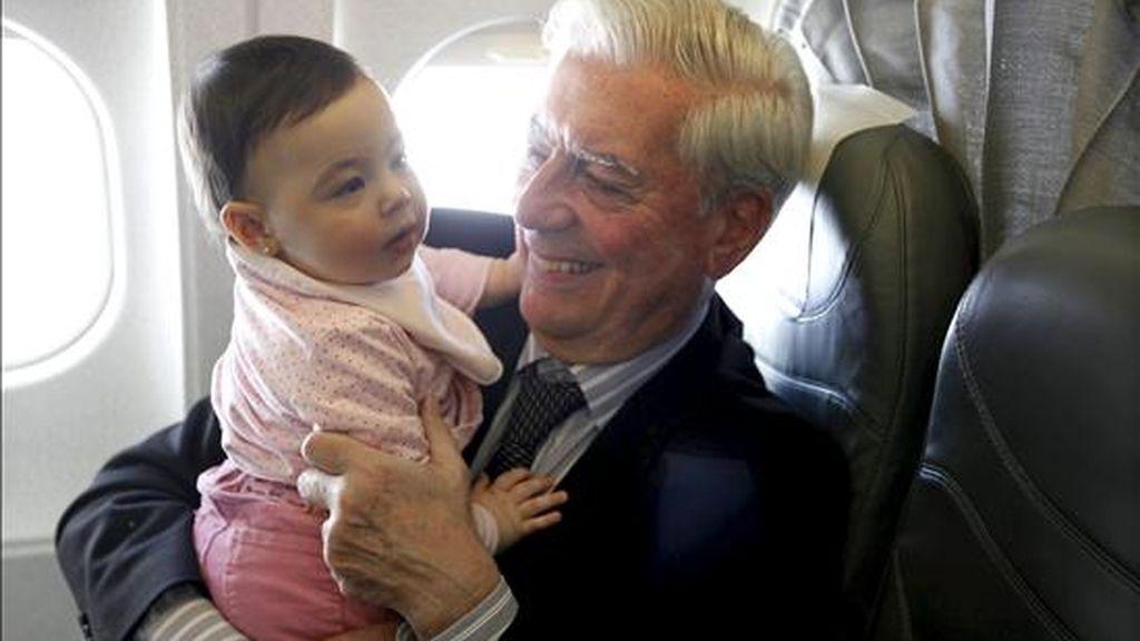 El escritor Mario Vargas Llosa juega con su nieta Anais durante el vuelo que le traslada a Estocolmo, donde el próximo viernes recibirá el Premio Nobel de Literatura. EFE