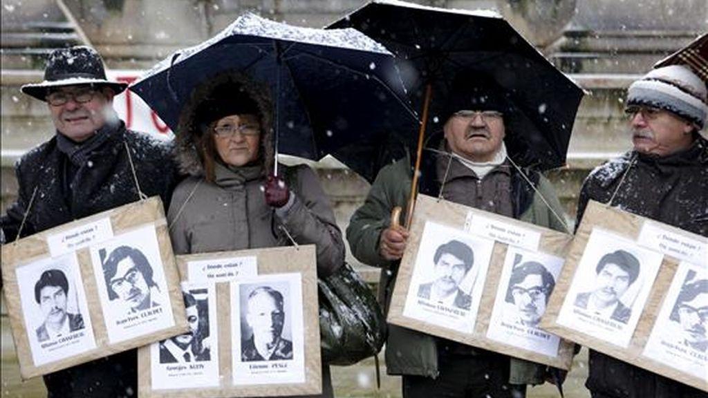 Familiares de víctimas de la dictadura chilena muestran fotos de sus seres queridos mientras participan en una manifestación en París (Francia). EFE