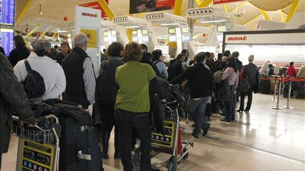 Decenas de turistas hacen cola en los mostradores de una compañía aérea esta tarde en el aeropuerto de Madrid-Barajas con motivo del inicio del puente de la Constitución. EFE