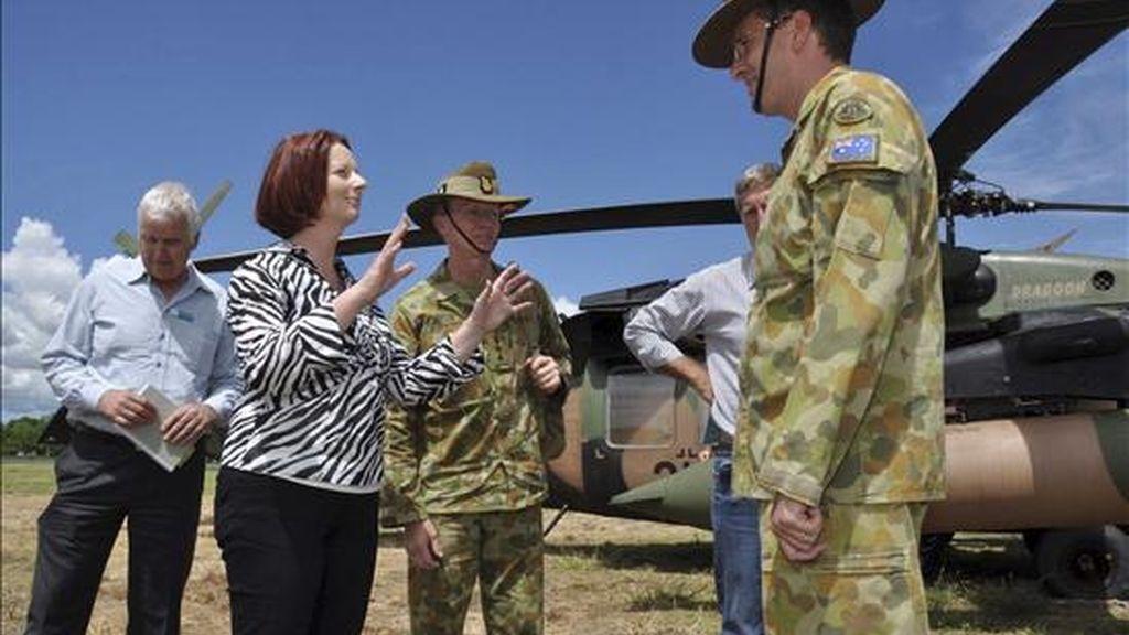 La primera ministra australiana, Julia Gillard, habla con los coroneles Luke Foster y Martin Bourquin (d) antes de sobrevolar hoy en helicóptero las zonas inundadas por el desbordamiento del río Fitzroy, desde Gladstone hasta Rockhampton, en Australia. EFE