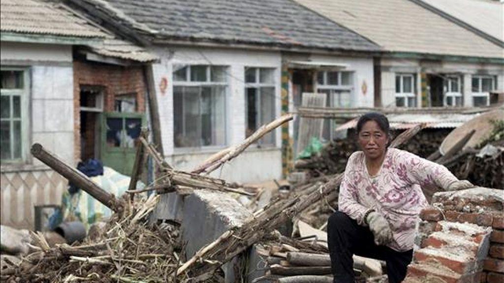 Una mujer descansa sobre los escombres de una de las casas dañadas por las inundaciones en Huadian, al noreste de la provincia china de Jilin. Las inundaciones causadas por las fuertes lluvias han provocado la huída de sus hogares de miles de personas damnificadas. EFE/Archivo