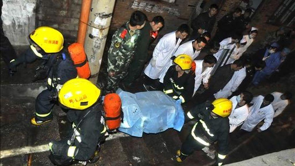 Miembros de los equipos de rescata trasladan el cuerpo sin vida de una de las víctimas de una explosión en un cibercafé en Kaili (China) hoy, 5 de diciembre de 2010. La explosión causó al menos seis muertos y 37 heridos, informó hoy la agencia oficial de noticias Xinhua. EFE