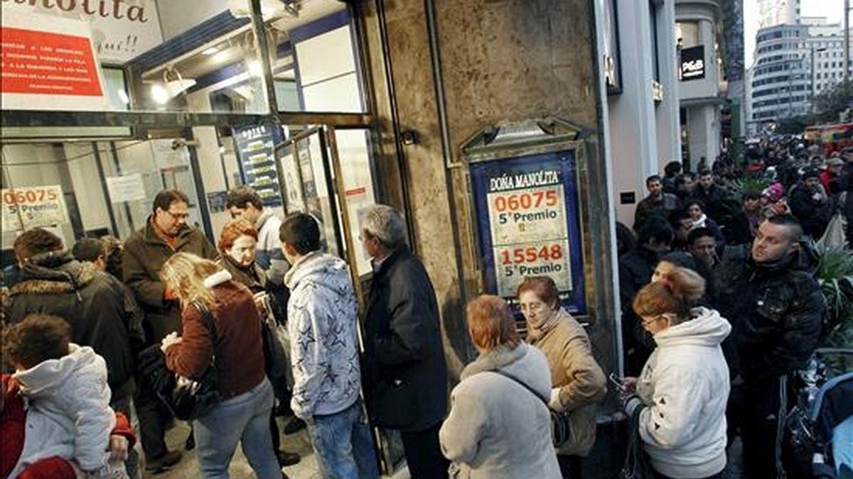 Personas guardando cola en una céntrica administración madrileña para comprar sus décimos dos días antes de la celebración del sorteo extraordinario del Niño. EFE