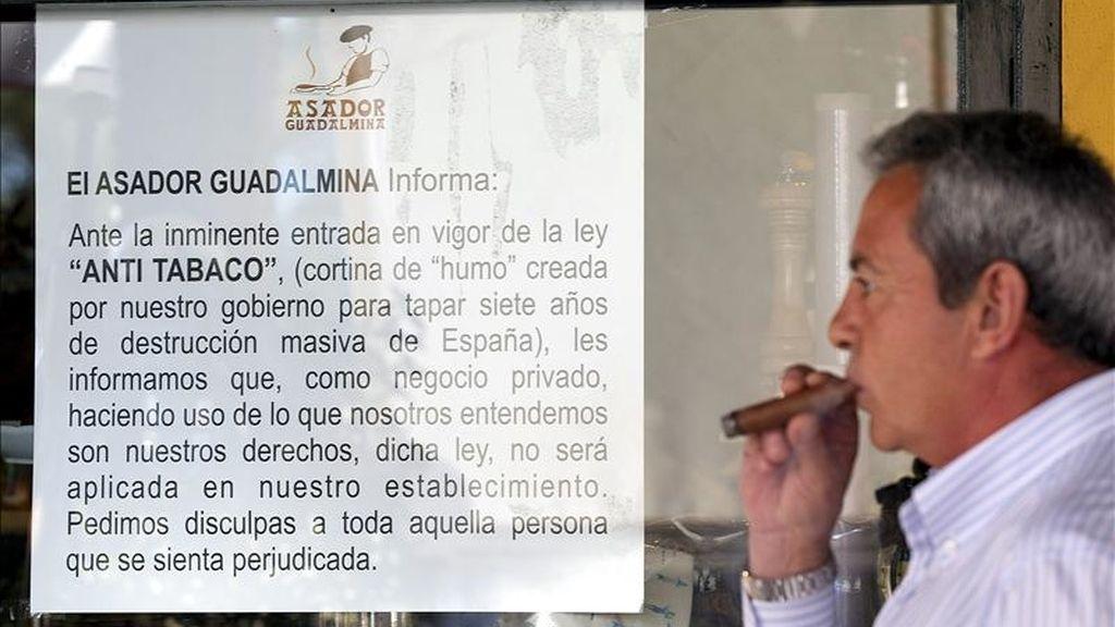 """El asador Guadalmina de Marbella (Málaga) donde han colocado carteles en la cristalera del establecimiento que da al exterior, en los que anuncia que no aplicará la nueva """"Ley antitabaco"""". EFE/Archivo"""
