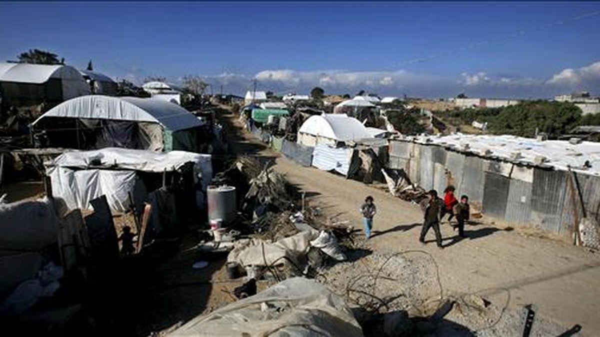 Niños palestinos caminan a lo largo de casas improvisadas en una de las zonas más pobres de la Franja de Gaza, el 5 de enero de 2011. Israel lanzó hoy un nuevo ataque con proyectiles que han causado la muerte a dos personas en Gaza. EFE