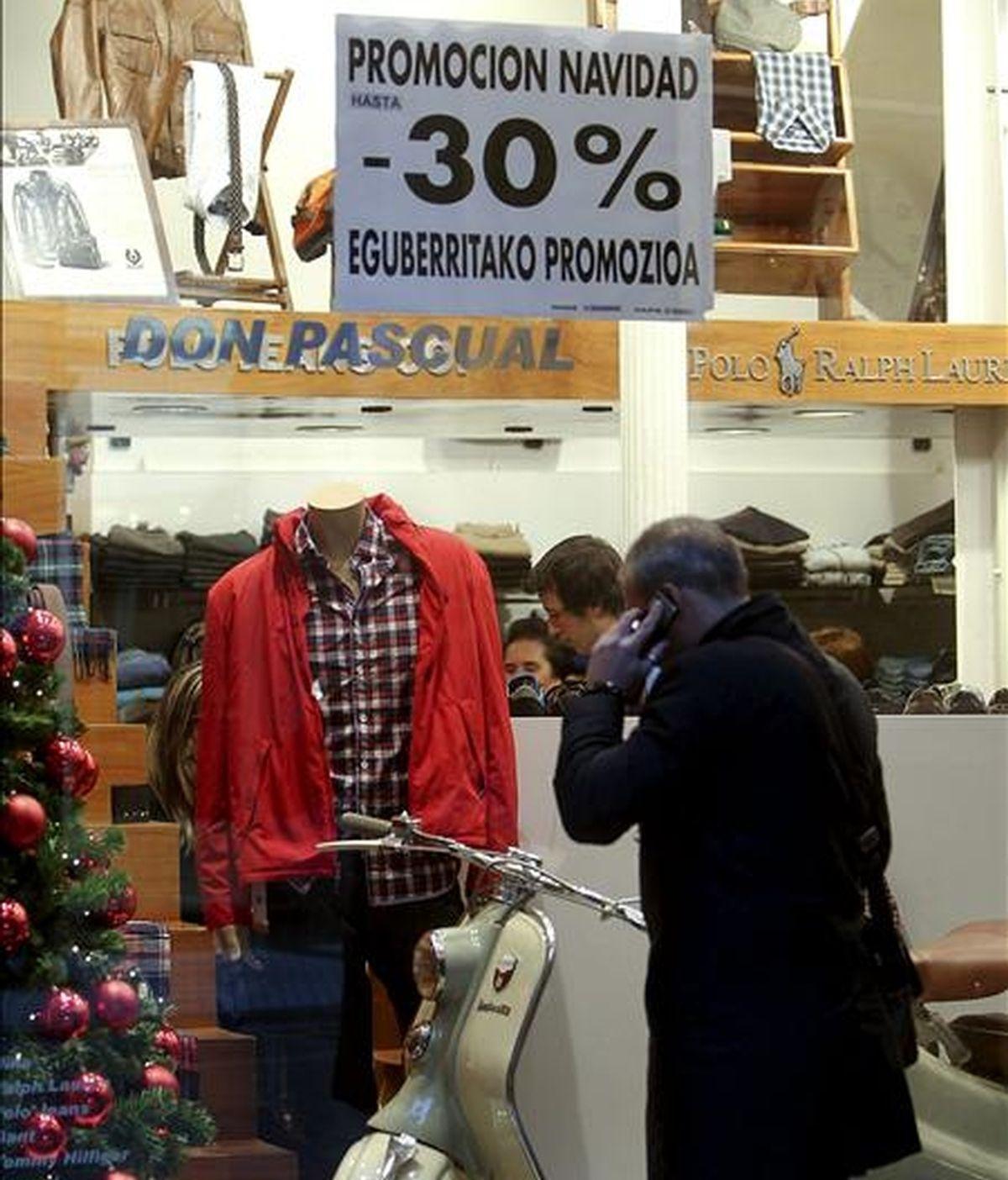 Un hombre pasa frente al escaparate de una tienda que presenta carteles de rebajas. EFE/Archivo
