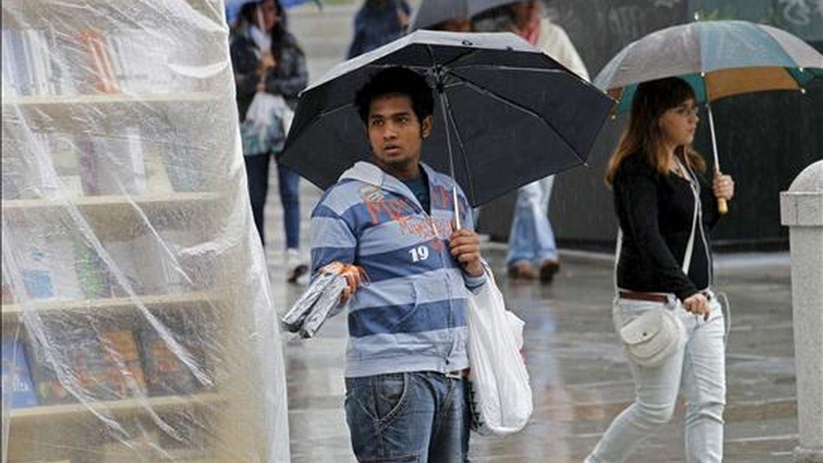 Un vendedor callejero ofrece paraguas a los viandantes en una calle de Madrid. EFE/Archivo