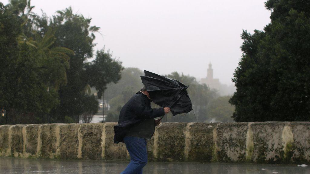 Hombre sujetando su paraguas por la fuerza del viento